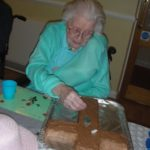 Clarence Park resident decorating the Easter cake