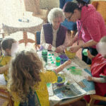 Little Pips and residents making sponge paintings for St Patrick's Day