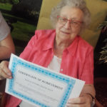 Casa di Lusso resident showing off her sign language course completion certificate