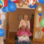 Teresa, Home Manager with Resident walking through the balloon arch on the red carpet