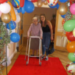 Resident with staff member walking through the balloon arch on the red carpet