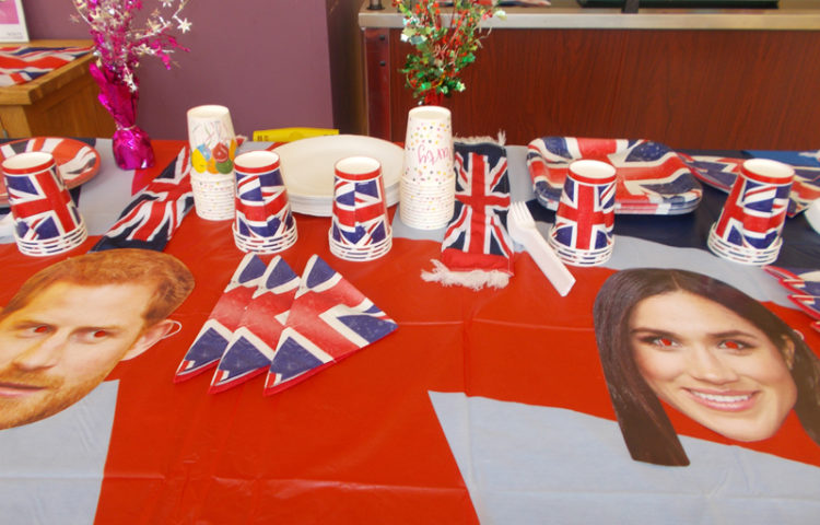 Table decorated in British flags and Harry and Meghan face masks