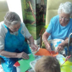 Residents and children painting butterfly pictures