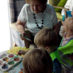 Resident and children painting butterfly pictures