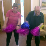 Kiddley Divey entertainer dancing with resident, both shaking glittered pom poms