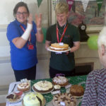 Immacolata house Care home domestic assistant, Ben with his medal and winning cake at their macmillan coffee morning