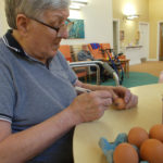 Resident painting eggs during La Fontana's June activities