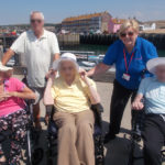 La Fontana Dementia Nursing Home residents and activities assistant a the harbour in Westbay Dorset