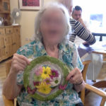 Immacolata House resident holding up her finished flower plate