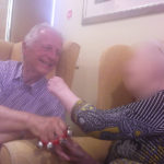 Immacolata House care home resident and loved one singing along to live entertainment from Flashback Theatre