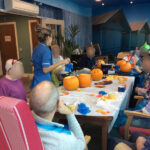 Casa di lusso care home residents and staff dressed for halloween while carving their pumpkins