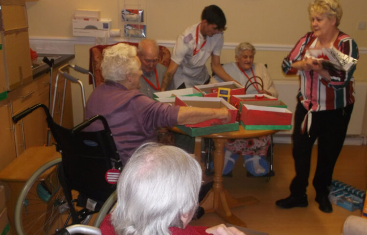 Residents and staff at Clarence Park Nursing Home decorating their shoe boxes ready to fill with gifts for the children