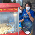 Casa di Lusso staff by the popcorn machine during their summer garden party
