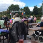 Casa di Lusso residents and staff enjoying the live music during their social distancing garden party