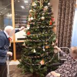 Casa di Lusso residents hanging decorations on the tree
