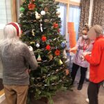 Casa di Lusso residents & staff member hanging decorations on the tree