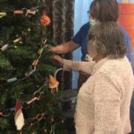 Casa di Lusso resident & activities coordinator hanging decorations on the tree