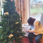 Campania resident decorating the 'covid friendly' tree